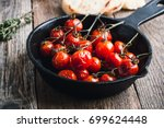 roasted cherry tomatoes in cast ... | Shutterstock . vector #699624448