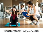 woman working out in a gym with ... | Shutterstock . vector #699677308