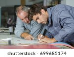 auto mechanic shows trainee how ... | Shutterstock . vector #699685174