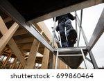 male carpenter moving down... | Shutterstock . vector #699860464