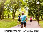 Small photo of Group of young athletes running in green sunny park.