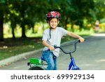 little boy learns to ride a... | Shutterstock . vector #699929134