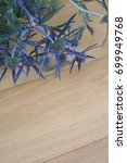 Small photo of Blue flowers of thistle amethyst eryngo on wooden background. Eryngium amethystinum. Selective focus.