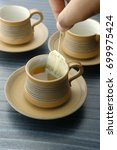 Small photo of Hand of man dripping tea bag in a tea cup on table