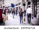 people walking down busy high...   Shutterstock . vector #699996718