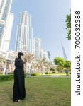 Small photo of Young lady in abaya standing outside with cell phone. Arab woman typing messages in the cell phone.