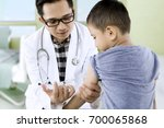 picture of little boy receiving ... | Shutterstock . vector #700065868