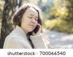 unhappy girl talking on the... | Shutterstock . vector #700066540