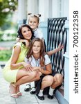 mother with two daughters is... | Shutterstock . vector #700122358