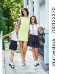 mother with two daughters is... | Shutterstock . vector #700122370