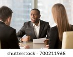 Small photo of Dissatisfied african-american boss clenching fist, scolding employees for bad work, displeased team leader holding report arguing with subordinates, defrauded cheated investor demanding money back