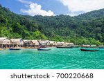 wooden boat and house on sea... | Shutterstock . vector #700220668