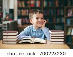 single loughing boy at the desk ... | Shutterstock . vector #700223230