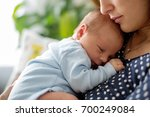 young mother  holding tenderly... | Shutterstock . vector #700249084