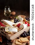 Small photo of Variety of different cheese with wine, fruits and nuts. Camembert, goat cheese, roquefort, gorgonzolla, gauda, parmesan, emmental, brie
