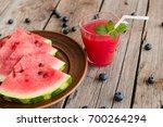 watermelon juice on a wooden... | Shutterstock . vector #700264294