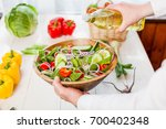 man pouring olive oil into... | Shutterstock . vector #700402348