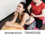Small photo of Pregnant woman enjoying a back massage from her midwife. Doula stroking a back of a smiling pregnant woman relaxing on a fitness ball.