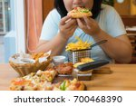 fat asian woman bite pizza and... | Shutterstock . vector #700468390