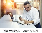 Small photo of Professional marketing expert in stylish optical writing information in notepad making research via smartphone.Prosperous male entrepreneur noting contact of banking service standing in office