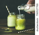 Small photo of Cold refreshing summer iced coconut matcha latte drink, hand pouring milk over glass. Selective focus, copy space, dark background, square crop. Clean eating, alkaline diet, dairy free food concept