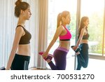 Small photo of Women group aerobic exercise in the indoor fitness gym class. Healthy lifestyle and wellness concept.