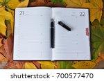 notebook  pen  leaves on wooden ... | Shutterstock . vector #700577470