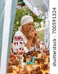 Small photo of ADYGEA, RUSSIA - AUGUST 19, 2017: woman plays music on a clay whistle in the shop with clay Souvenirs and toys at the festival of cheese Adyghe in Adygea