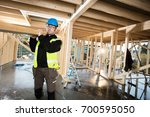 carpenter in protective jacket... | Shutterstock . vector #700595050