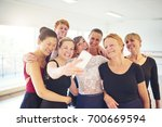 Small photo of Mixed age group of women laughing while standing arm in arm together taking a selfie during ballet class