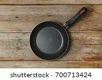 empty frying pan on a wooden... | Shutterstock . vector #700713424