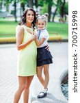 mom and daughter are walking in ... | Shutterstock . vector #700715998