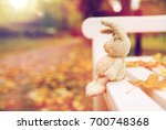 Stock photo season childhood and loneliness concept lonely toy rabbit on bench in autumn park 700748368