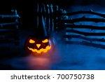 glowing spooky pumpkin in black ... | Shutterstock . vector #700750738