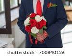 groom hand holding bouquet  | Shutterstock . vector #700840126