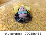 An adult female has her entire body covered and buried in corn kernels in a corn pit, with only her head showing