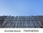 Small photo of Wooden fence on clear blue sky background. Bamboo tree railing barrier image with empty copy space on summer day. Close up part of rural yard exterior, helps to protect land and ensure safety