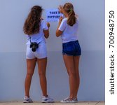 two girls posting a sign to... | Shutterstock . vector #700948750