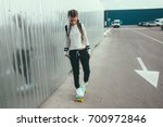11-12 years old tween girl wearing fashion sportswear rollerskating on skateboard in the city street, urban hipster style
