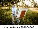 Small photo of Artists Sketching in the garden. Male artist on painting on canvas in outdoor. Fine art artist. Male artist working on painting