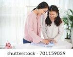 mother teaching her daughter... | Shutterstock . vector #701159029
