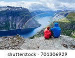 couple sits on rock and looks...   Shutterstock . vector #701306929
