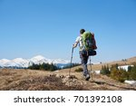 Small photo of Rearview low angle shot of an adventurous man wearing backpack using hiking sticks while walking the mountain copyspace travelling adventure nature landscape sport activity