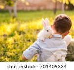 Stock photo boy embracing his rabbit in the garden 701409334