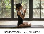 Young attractive woman practicing yoga at home, sitting in Virasana exercise, Hero pose with namaste, working out wearing sportswear, black shorts, top, indoor full length, side view studio background