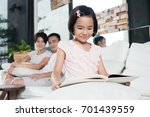 young asian girl reading a book ... | Shutterstock . vector #701439559