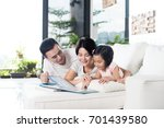 Young Asian Family Reading A...
