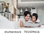 young asian mother reading a... | Shutterstock . vector #701439616