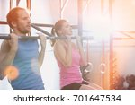 man and woman doing pull ups in ... | Shutterstock . vector #701647534