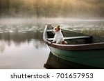 Stock photo small dog in a wooden boat on the lake breed jack russell terrier 701657953